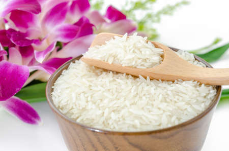 Raw rice jasmine and wooden spoon in wooden bowl with violet orchid flower on white background.