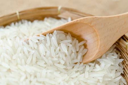 arroz blanco: Arroz blanco sin procesar y cuchara de madera en la armadura de cesta sobre fondo saco.