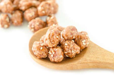 white sesame seeds: Honey roasted coated peanuts and white sesame seeds in spoon wooden on white background.
