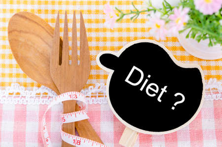 crave: Diet wood tag and wood spoon, on beautiful fabric background. Stock Photo