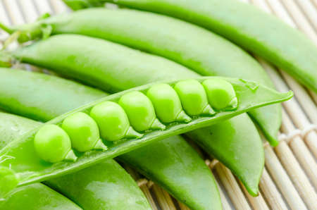 sweet sugar snap: Fresh green peas pods on bamboo mat background. Stock Photo