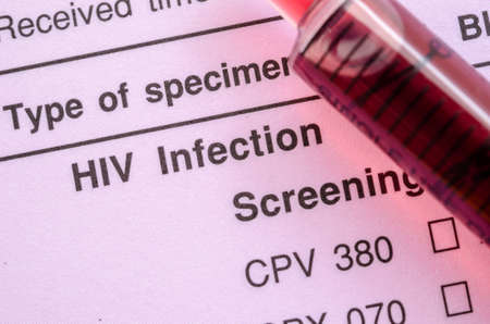 Sample blood in syringe on HIV infection screening test form.