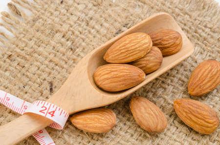metro medir: Almond and measuring meter on sack background. Diet concept. Foto de archivo
