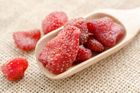 freeze dried: Dried strawberries in wooden spoon on sack background.