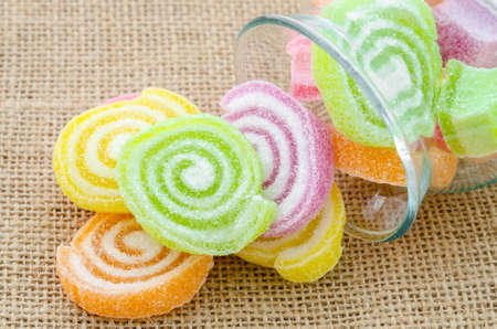 sparce: Sweet sugar candies in glass bottle on sack background.