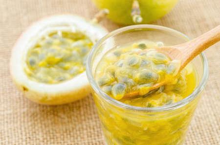 pasion: Jugo de maracuyá en vidrio y fruta de la pasión fresca en fondo del saco.