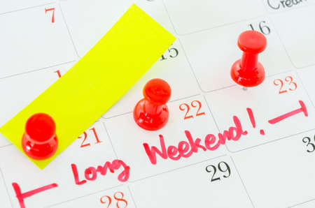 long shot: Concept image of a Calendar with a red push pin. Closeup shot of a thumbtack attached. The words Long Weekend written on a white calendar to remind you an important appointment. Stock Photo