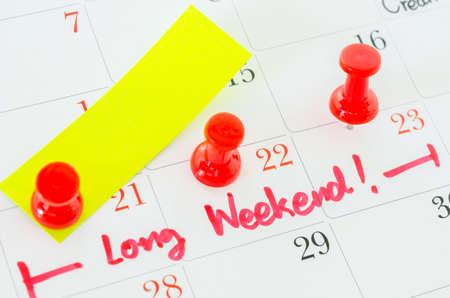 Concepto de imagen de un calendario con un alfiler rojo. El primer tiró de una chincheta adjunto. Las palabras escritas largo fin de semana en un calendario blanco para recordarle una cita importante.