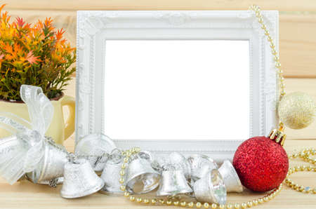 photo: Vintage white blankk photo frame with chirstmas decorations on wood background. Save clipping path.