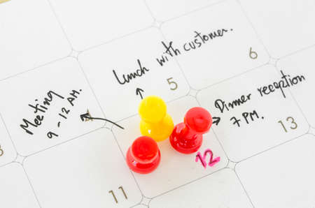 booked: Pushpin on calendar with busy day overworked schedule.