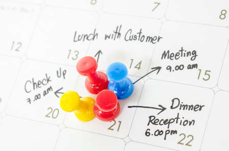 Pushpin on calendar with busy day overworked schedule.