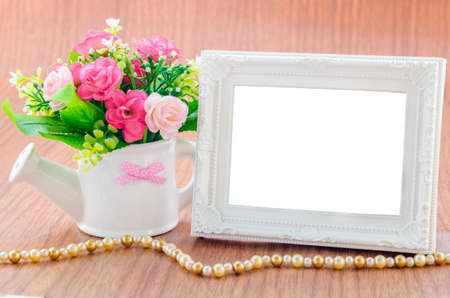 blank photo: Flowers vase and vintage white picture frame on wooden desktop, clipping path