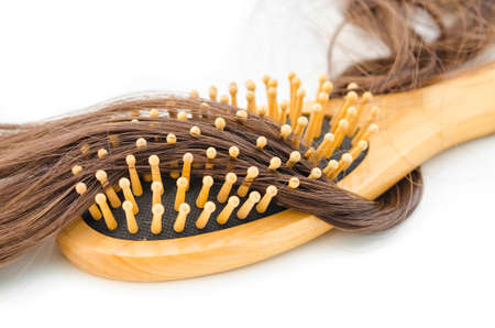 Hair loss problem concept. Wooden hair brush and hair fall on white background. Standard-Bild