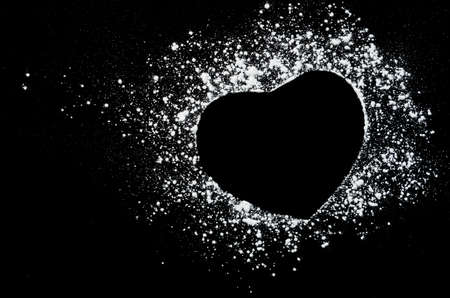 dust cloud: Freeze motion of white powder on black dark background. Abstract design of dust cloud. Particles heart shaped explosion screensaver, wallpaper with copy space. Love, passion, care concept
