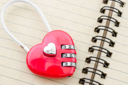 open diary: Red master key heart shape lock on open diary. Stock Photo