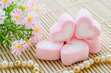 sweet background: Sweet heart shape of pink marshmallows with flower on mat wooden background,decoration for love and valentine day concept.