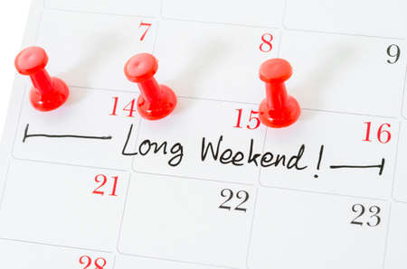 long weekend: Concept image of a Calendar with a red push pin. Closeup shot of a thumbtack attached. The words Long Weekend written on a white calendar to remind you an important appointment. Stock Photo