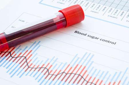 Sample blood for screening diabetic test in blood tube on blood sugar control chart. Foto de archivo