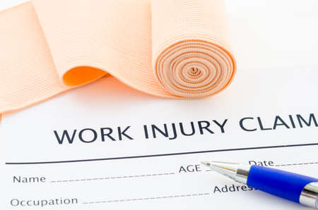 risky job: Work injury claim form showing business insurance concept and medical bandage roll with pen.