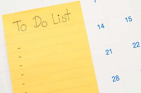 Handwritten To do list in stick note on calendar.