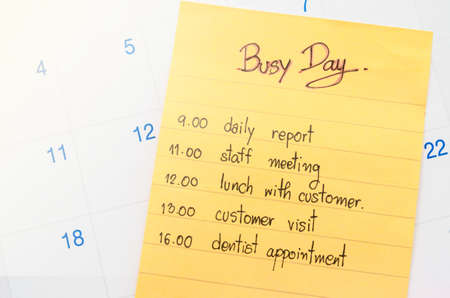 booked: Busy day and plan in yellow stick note on calendar.