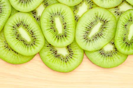 freshest: Many slices of kiwi fruit on wooden background.
