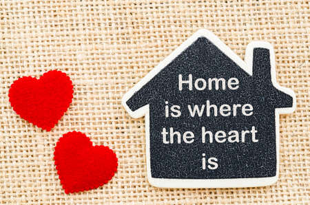 where: Home is where the heart is word in wooden home model with red heart on sack background. Stock Photo