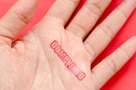 dissertation: Completed stamp in hand on red background. Success concept. Stock Photo