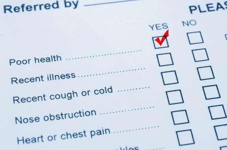 evaluacion: Mano que pone la marca de verificación con marcador rojo en pobres de la Salud formulario de evaluación de estado. Foto de archivo