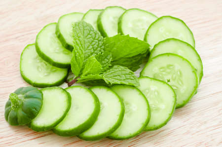 cucumber slices with mint leaf on wooden background