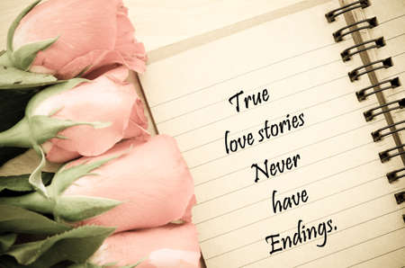 endings: True love stories never have endings handwriing on diary note with roses on wooden background with a vintage style filter effect. Stock Photo