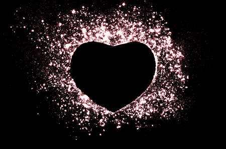 love blast: Freeze motion of heart shaped red powder isolated on black, dark background. Abstract design of dust cloud. Particles explosion screen saver, wallpaper with copy space. Love, passion, feelings concept.