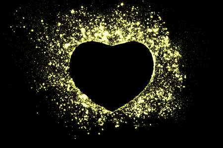 love blast: Freeze motion of heart shaped yellow powder isolated on black, dark background. Abstract design of dust cloud. Particles explosion screen saver, wallpaper with copy space. Love, passion, feelings concept. Stock Photo