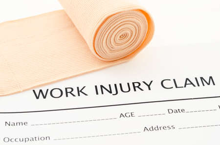 compensate: Claim form for an injury at work with medical bandage.