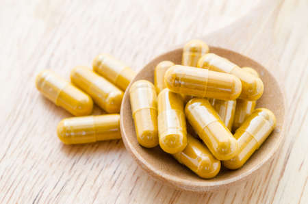 nutritional therapy: Vitamin capsules in a wooden spoon on a wooden background.