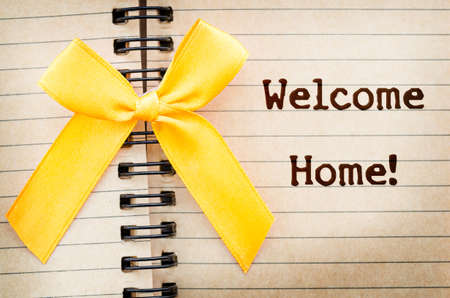 welcome home: The words Welcome Home written on a old brown diary paper next to a yellow ribbon,in reference to military returning from overseas duty. Stock Photo