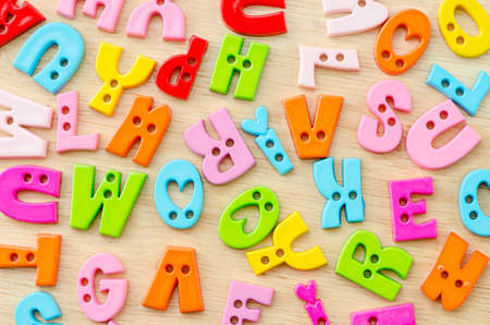 untidy: Untidy collection of plastic alphabet letters, school education toy on wooden background.