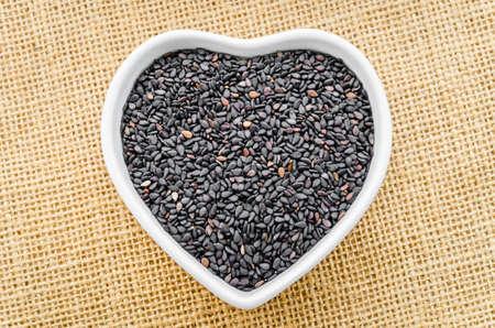 serine: Black Sesame in white bowl on sack background. Stock Photo