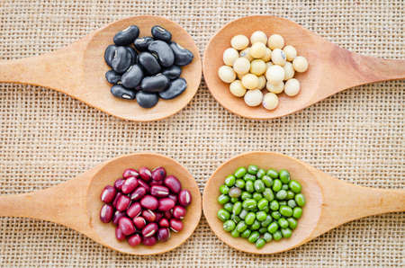 azuki bean: Mix from different beans, black bean, soy bean, azuki bean, mung bean in wooden spoon on the sackcloth background Stock Photo