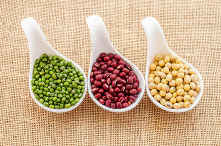 munggo: Mix of seeds beans, green bean, azuki or red bean, soy bean on in white spoon on sack background.