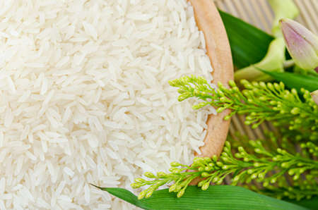 raw white rice in a bowl with flower - top view