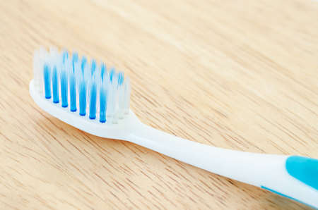 purge: Close up blue color toothbrush on wooden background.