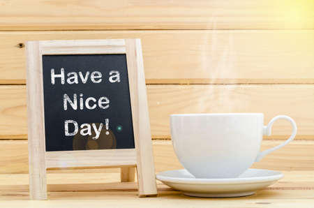 slateboard: Have a nice day word on chalkboard and coffee in white cup with smoke.