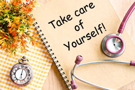 Abbi cura di te sul libro del diario e stetoscopio con orologio da tasca sul tavolo.