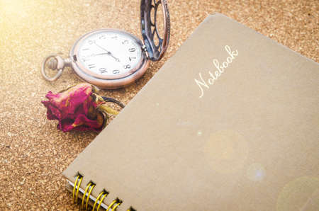 old diary: The old diary with dry red roses and pocket watch on wood table. Stock Photo