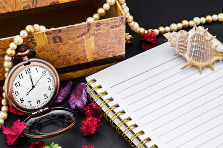 open diary: Open diary and vintage pocket watch with decorate on black background.