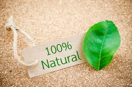 environmentalist label: 100% Natural word on recycle brown tag with green leaf on wooden background.