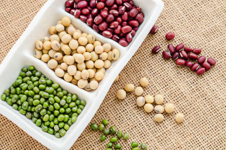 munggo: Mix of seeds beans, green bean, azuki or red bean, soy bean on in white bowl on sack background.