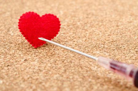 immunize: Red heart and needle syringe on wooden background.