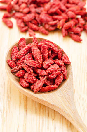 superfruit: Wooden tablespoon of dried goji berries on wood table.